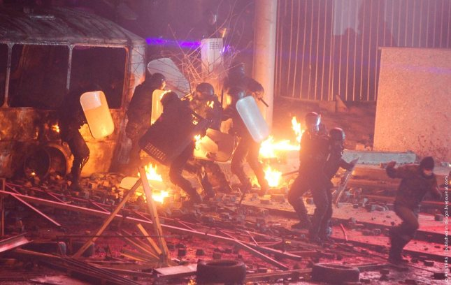 Ukranian riot police take cover from incendiary devices thrown by pro-European protesters during a rally in Kiev